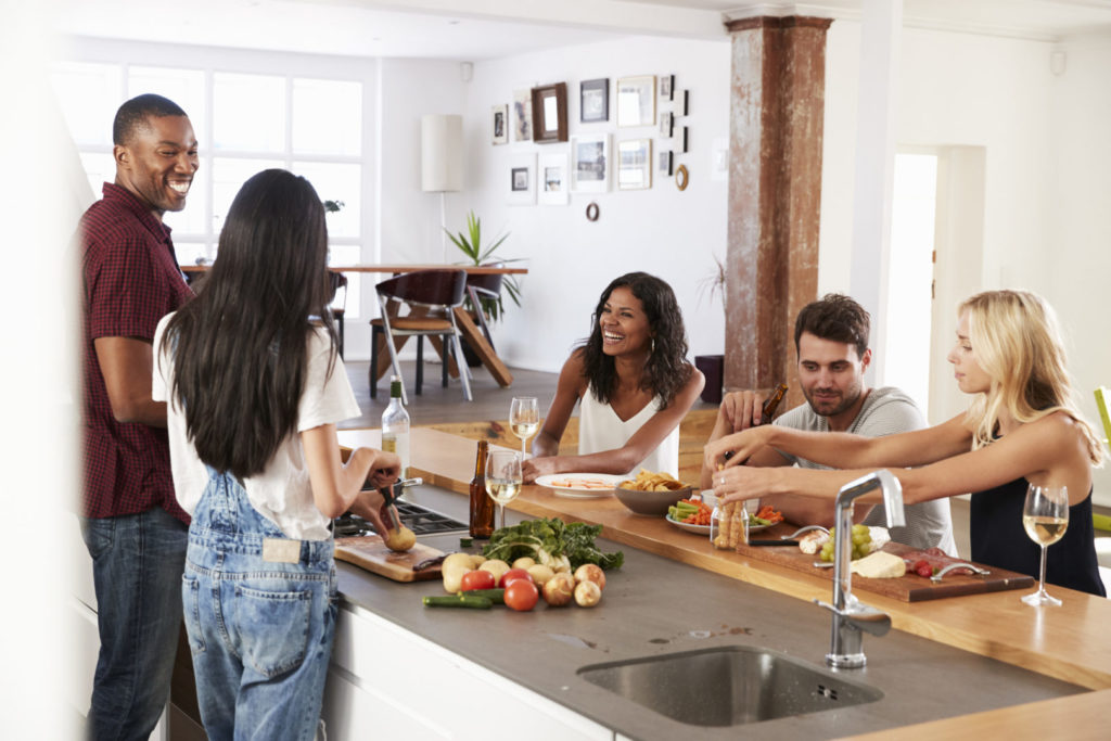 group of freidns chatting at a kitchen counter