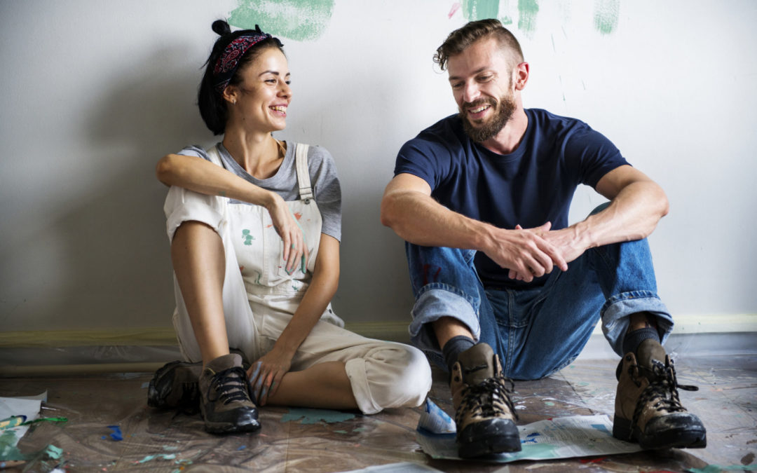 a couple sitting on the floor in paint spattered renovation clothing having a chat
